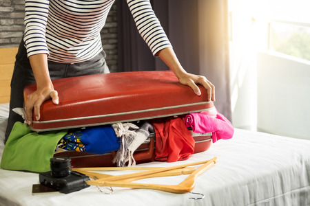 Woman trying to fit all clothing to packing her red suitcase before vacation