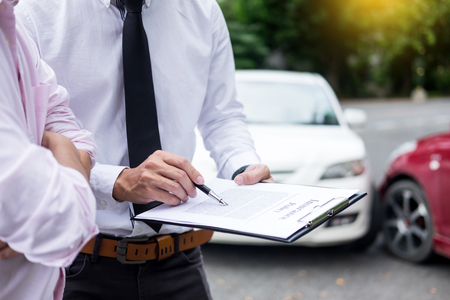 Insurance agent writing on clipboard while examining car after accident claim being assessed and processed