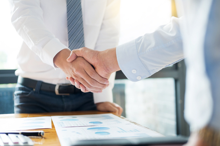 Sealing a deal! Business people shaking hands after Welcoming partners  finishing up a meeting or setting goals and planning way to success in the office