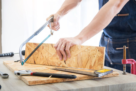 Carpenter working carefully looking at the plans work in carpentry. He is successful entrepreneur at his workplace. hammering a nail Supports On Building Site work with cutter Stock Photo