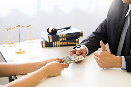 Lawyer being offered receiving money as bribe from client at desk in courtroom Stock Photo