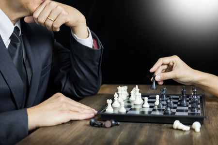 hand of businessman moving chess figure in competition board game for development analysis, strategy idea management or leadership concept