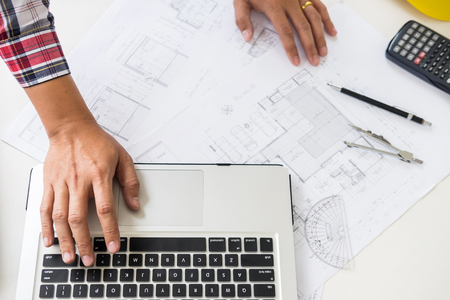 Close-up Of Person's engineer Hand Drawing Plan On Blue Print with architect equipment, Architects discussing at the table, team work and work flow construction concept. Stock Photo