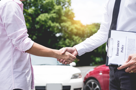 Customer shake hand with auto insurance agents examining car crash owner after agreeing find a friendly agreement after a car accident to terms of insurance On the road.