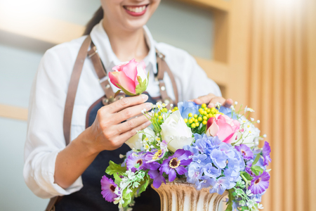 Female Florist at work using Arranging making beautiful Artificial bouquet vest at flower shop, business, sale and floristry craft and hand made concept