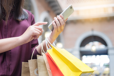Woman look at mobile phone with paperbags in the mall while enjoying a day shopping
