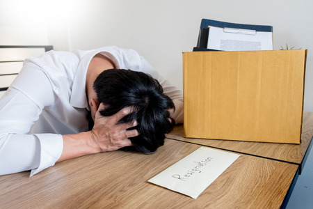 Businessmen are holding resignation document and packing personal company on brown cardboard box changing work, unemployment or resign concept.