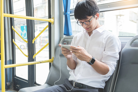 Passenger transport. people in the bus. man rides a bus, listening or calling to music and typing a message while riding home