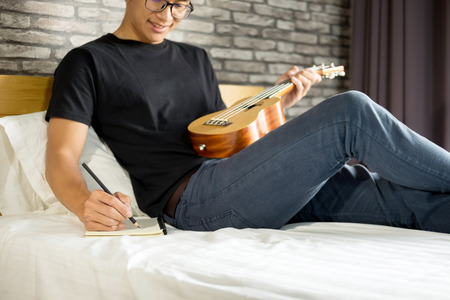 Happy young asian man playing ukulele sitting on bed in bedroom