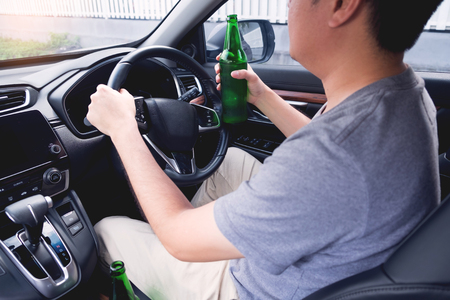 Don't Drink for Drive concept, Young Drunk man drinking bottle of beer or alcohol during driving the car dangerously. Standard-Bild - 121285807