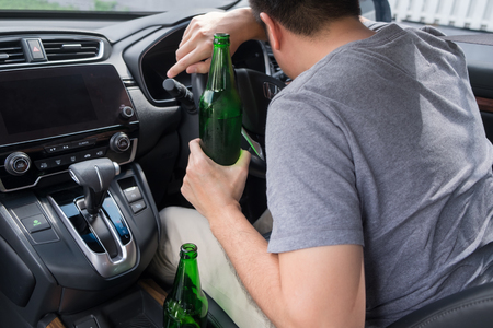 Don't Drink for Drive concept, Young Drunk man drinking bottle of beer or alcohol during driving the car dangerously. Standard-Bild - 121285961