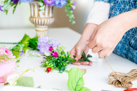 young women business owner florist making or Arranging Artificial flowers vest in her shop, craft and hand made concept. Stock Photo