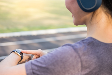 Women exercise in the morning using looking on her smart watches active sports activity on her hand