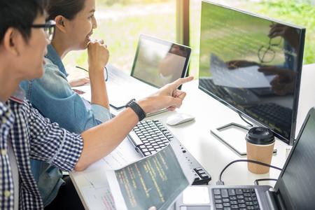Team asiatico Sviluppatore in outsourcing Guardando il codice di programmazione dello schermo che lavora con il software del computer portatile