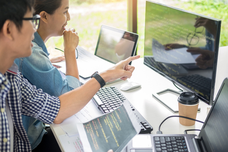 Zespół azjatycki Outsource Developer Patrząc na kod programowania ekranu pracujący z oprogramowaniem do laptopa