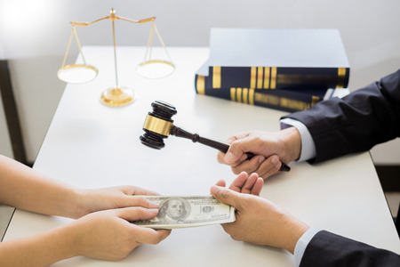 Lawyer being offered receiving money as bribe from client at desk in courtroom 写真素材