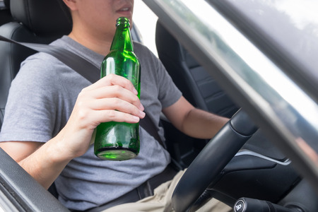 Dont Drink for Drive concept, Young Drunk man drinking bottle of beer or alcohol during driving the car dangerously.