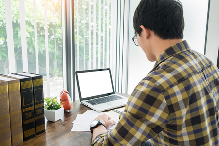 young caucasian man working at home planning work writing note on some project with his laptop on a desk, strartup business, e learning concept. 写真素材 - 124719549