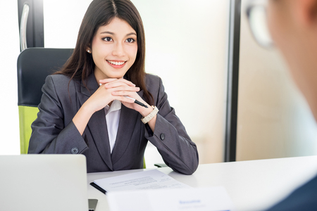 Female Manager conducting a job interview with female applicant looking at her quizzically with her CV in her hand and Talking to her Subordinate at her Table Inside the Office 스톡 콘텐츠 - 124719790