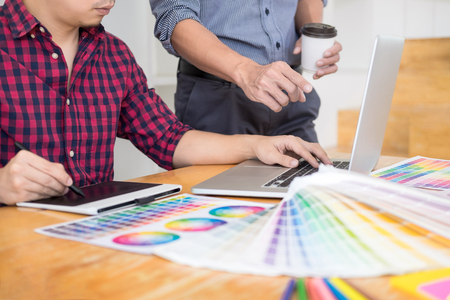team interior designer drawing a new project using graphic computer and choosing Color swatch samples in modern Creative studio Stock Photo - 124719876