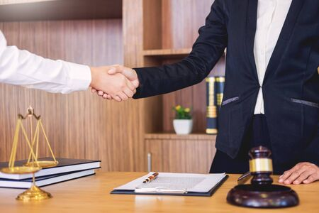 Gavel Justice hammer on wooden table with judge and client shaking hands after adviced in background at courtroom, lawyer service concept Stok Fotoğraf - 124720191