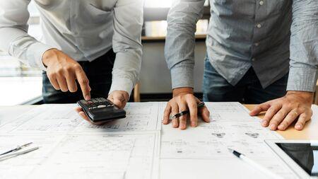 Une équipe d'ingénieurs confiante travaillant avec Blue Print avec des équipements d'architecte discutant et planifiant un projet de construction de flux de travail. avec un partenaire à la table sur le site de travail de bureau.