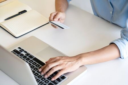 Man holding credit card in hand and entering security code using smart phone on laptop keyboard, online payment shopping concept.
