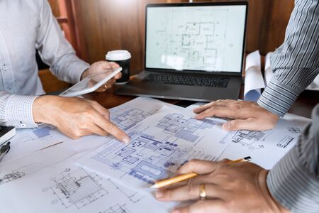 Confident engineer team working with Blue Print with architect equipment discussing and Planning work flow construction project. with partner at the table in office work site.