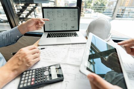 Real-estate concept, Two engineer and architect discussing blueprints data working and digital tablet on construction building project Banque d'images - 129290299