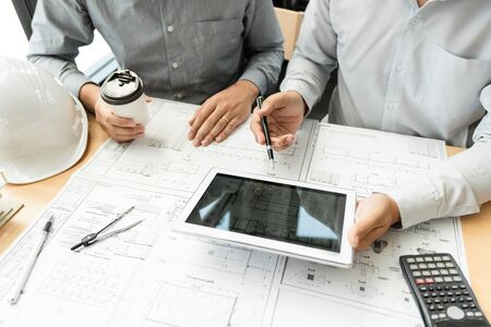 Real-estate concept, Two engineer and architect discussing blueprints data working and digital tablet on construction building project Banque d'images - 129290391