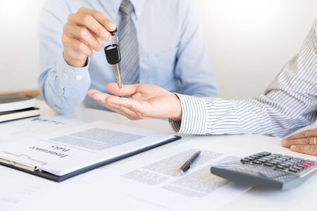 business man agent offer insurance form clipped to pad and silver pen to sign closeup. Certificate of motor insurance and policy schedule with car key, consultant signing car  contract. Stock Photo