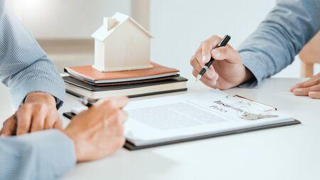 agente broker e cliente che tiene la penna, l'assicurato e spiega la discussione per quanto riguarda l'offerta di prestito ipotecario e l'assicurazione sulla casa