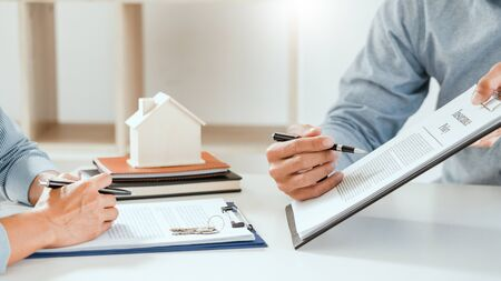 broker agent and customer holding pen, the policyholder and explain discussing for concerning mortgage loan offer for and house insurance