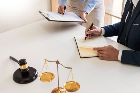 Male lawyer or judge consult with client check contract papers recommend legal proposals, Law services concept. Фото со стока