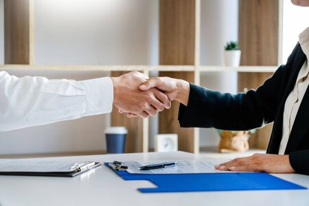businessman and businesswoman handshaking over the office desk after Greeting new colleague, business meetings concept