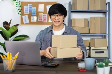 Asian business man startup SME entrepreneur or freelance working in a cardboard box prepares delivery box for customer, Online selling, e-commerce, packaging and shipping concept Stock Photo