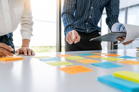 Business people arranging sticky notes commenting and brainstorming on work priorities colleague in a modern co-working space