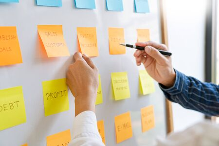 young business workers posting with sticky notes stickers reminders creative brainstorming at board the colleague in a modern co-working space Foto de archivo