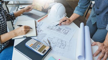 Cooperation Corporate designers in the office are working on a new project Planning blueprint Design at construction site at desk in office