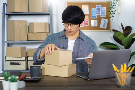 Asian man entrepreneur startup small business entrepreneur SME freelance man working with box to online marketing packaging and delivery scene at home office, online business seller concept Stock Photo