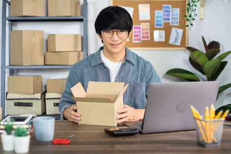 Asian business man startup SME entrepreneur or freelance working in a cardboard box prepares delivery box for customer, Online selling, e-commerce, packaging and shipping concept Stok Fotoğraf