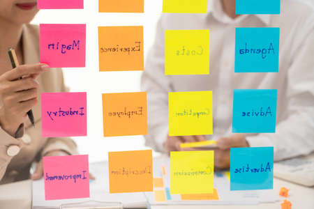 business people planning startup project placing sticky notes session to share idea on glass wall, Strategy Analysis Office Concept Stock Photo