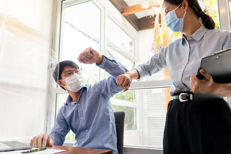Two Asian colleagues in medical masks avoid a handshake when meeting in the office greeting with bumping elbows during coronavirus COVID-19 epidemic in office, Social distancing concept