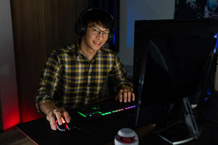 Handsome excited asian gamer guy in headphones enjoy and rejoicing while playing video games on computer in cozy room is lit with warm and neon light, gaming and technology e-sport concept. Stockfoto