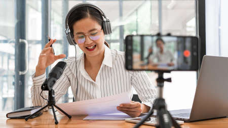 Asian women podcaster podcasting and recording online talk show at studio using headphones, professional microphone and computer laptop on table looking at camera for radio podcast. Banco de Imagens