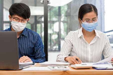 Group of Teamwork Asian business People Wearing Protective face Mask In Office During Pandemic coronavirus COVID-19, New Normal and Social distancing concept.