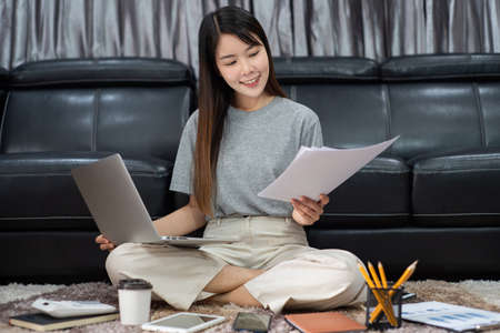 Attractive young beautiful asian woman Entrepreneur or freelancer working at home with laptop business reports and online communications on living room sofa, working remotely access concept