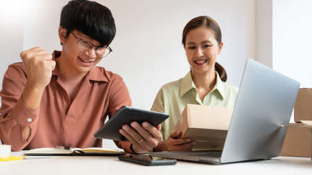 Asian business couple owner working at home with packing box of their online store prepare to deliver products to customers, alpha generation life style concept 版權商用圖片
