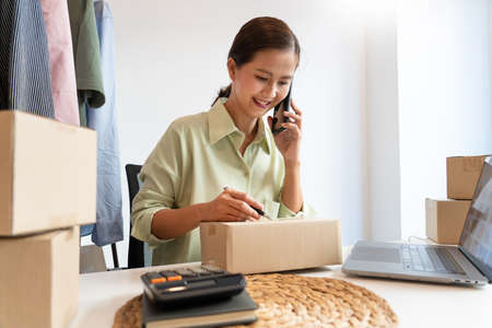 Asian business owner working at home with packing box of her online store prepare to deliver products to customers, alpha generation life style concept Imagens