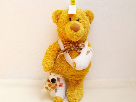 nursing association: sick teddy with plaster and bandage on the arm is measured